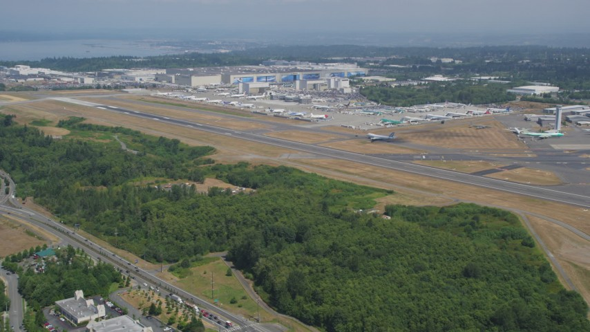 5K stock footage aerial video fly over trees to approach Paine Field and  the Boeing Factory, Everett, Washington
