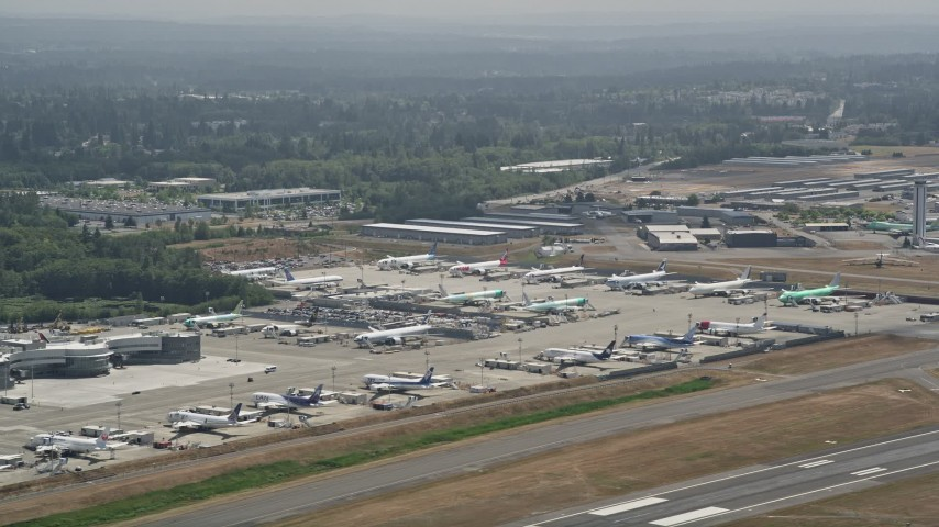 5K stock footage aerial video of passing by parked airliners at Paine Field, Everett, Washington Aerial Stock Footage | AX45_137