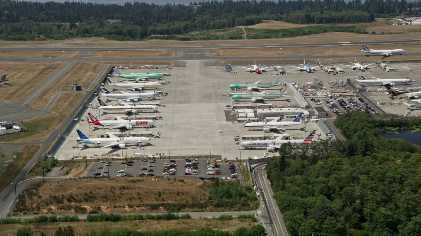 5K stock footage aerial video of approaching parked airliners at Paine Field, Washington Aerial Stock Footage | AX45_143