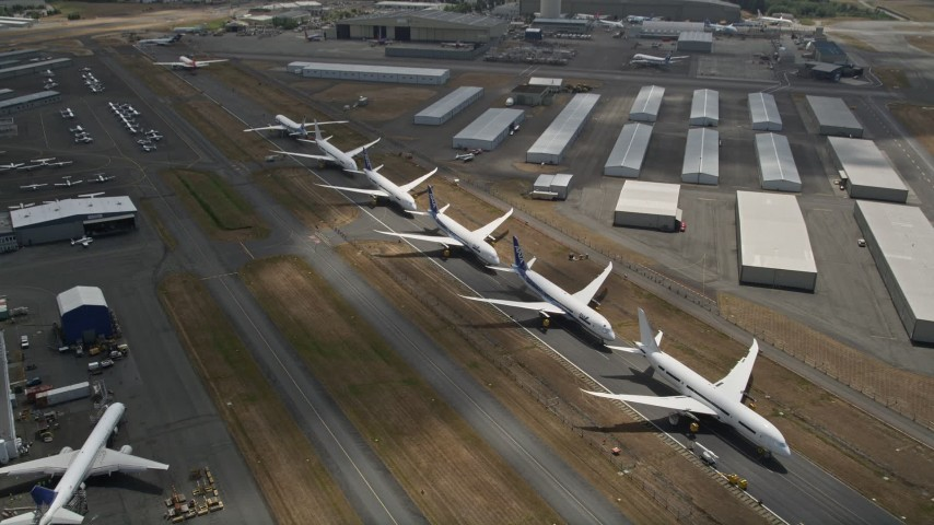 5K stock footage aerial video approach and fly over a row of parked airliners, Paine Field, Washington Aerial Stock Footage   AX46_003