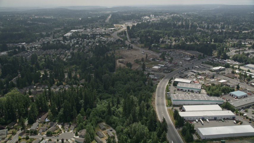 5K stock footage aerial video follow road between homes and warehouse buildings to approach a mobile homes park, Lynnwood, Washington Aerial Stock Footage | AX46_005