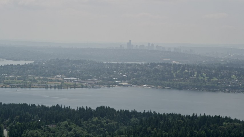 5K stock footage aerial video of skyline in fog seen from tree-lined lake shores, Seattle, Washington Aerial Stock Footage | AX46_019