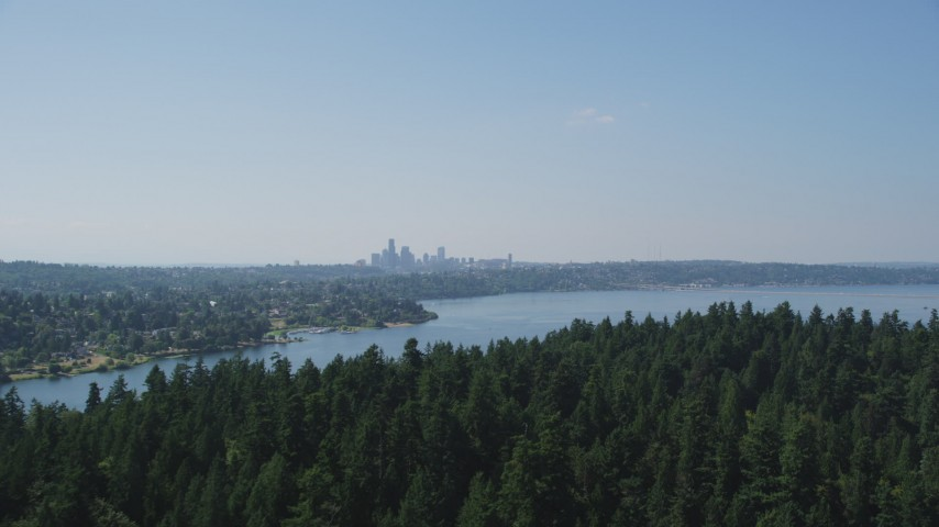 5K stock footage aerial video fly over tree covered Bailey Peninsula to reveal Downtown Seattle skyline, Washington Aerial Stock Footage | AX47_005
