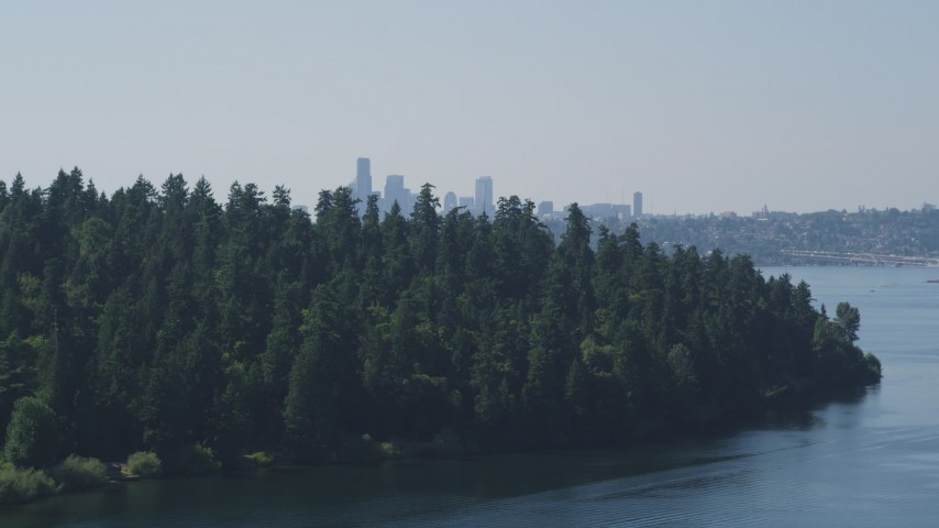 5K stock footage aerial video of Downtown Seattle skyline in the far distance beyond the tree-covered Bailey Peninsula, Washington Aerial Stock Footage | AX47_007