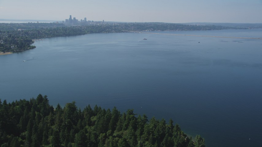 5K stock footage aerial video fly over Lake Washington to approach bridge and the Downtown Seattle skyline in Washington Aerial Stock Footage | AX47_009