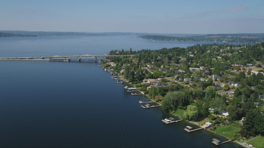 5K aerial video flyby lakeside homes toward a bridge spanning Lake Washington, Mercer Island, Seattle, Washington Aerial Stock Footage | AX47_010
