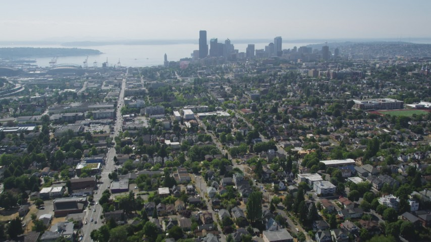 5K stock footage aerial video tilt from park to reveal urban homes in Central Seattle and the Downtown Seattle skyline, Washington Aerial Stock Footage | AX47_015