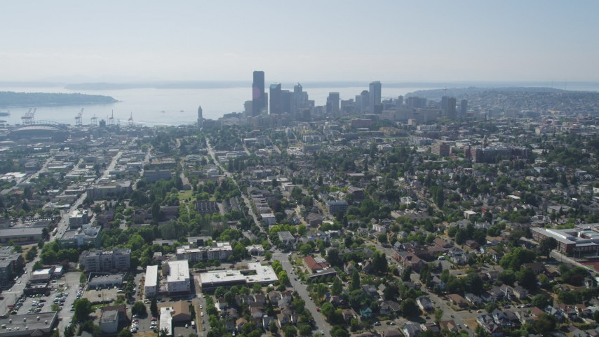 5K stock footage aerial video fly over urban homes in Central Seattle to approach Downtown Seattle skyline, Washington Aerial Stock Footage | AX47_016