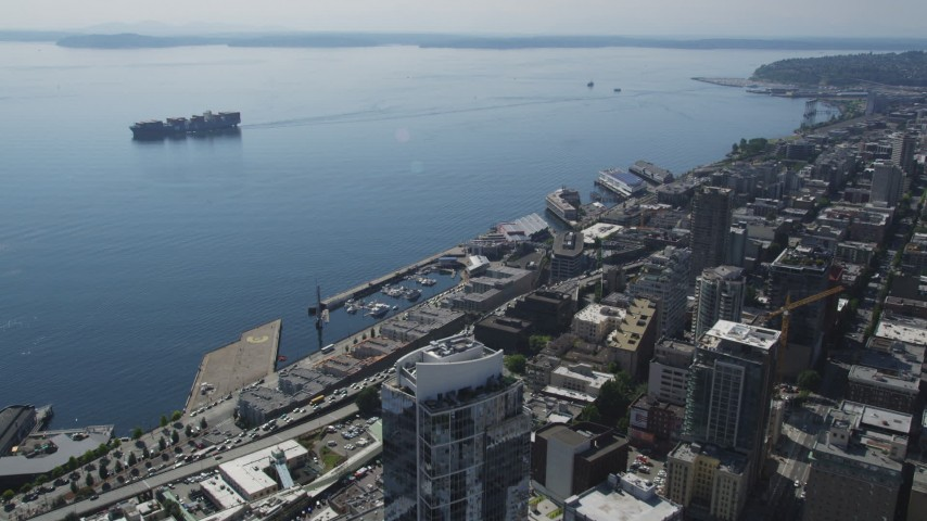 5K stock footage aerial video fly over Central Waterfront in Downtown Seattle to approach cargo ship sailing Elliott Bay, Washington Aerial Stock Footage | AX47_022