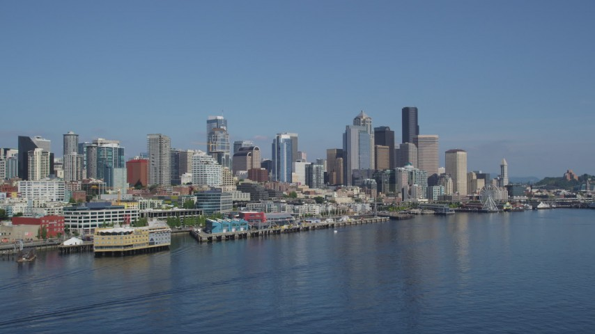 5K stock footage aerial video of Downtown Seattle skyline and Central Waterfront piers seen from Elliott Bay, Washington Aerial Stock Footage | AX47_032