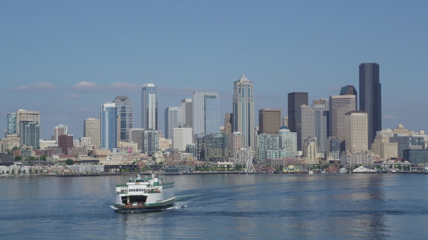 5K stock footage aerial video orbit a ferry sailing on Elliott Bay to reveal the Downtown Seattle skyline, Washington Aerial Stock Footage | AX47_034