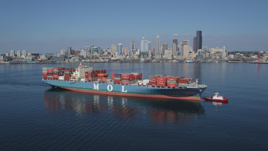 5K stock footage aerial video flyby a cargo ship and tugboat with the Downtown Seattle skyline in the background, Washington Aerial Stock Footage | AX47_035