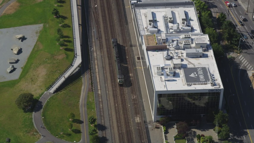 5K stock footage aerial video track a commuter train passing a park in the Seattle Waterfront in Downtown Seattle, Washington Aerial Stock Footage | AX47_062