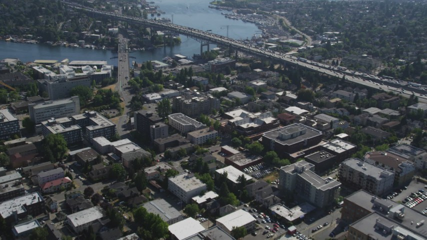 5K stock footage aerial video fly over an office building, tilt to reveal the bridge, Lake Union, and Downtown Seattle skyline in Washington Aerial Stock Footage AX47_079 | Axiom Images