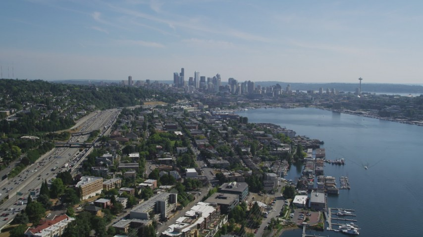 5K stock footage aerial video follow the shore of Lake Union to approach the Downtown Seattle skyline, Washington Aerial Stock Footage | AX47_081