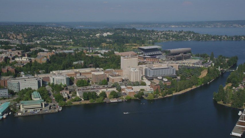 5K stock footage aerial video fly over Portage Bay to approach the University of Washington campus and Husky Stadium in Seattle, Washington Aerial Stock Footage | AX47_083