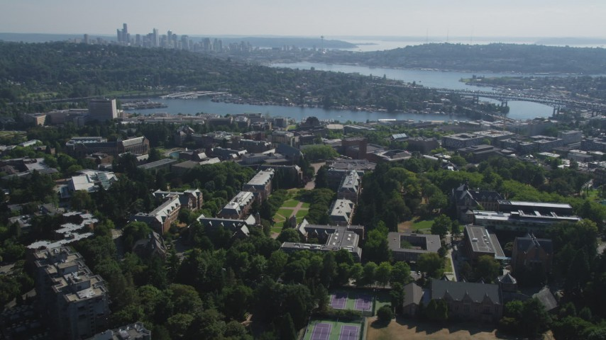 5K stock footage aerial video tilt from the University of Washington campus to reveal Portage Bay, Lake Union, and the skyline of Downtown Seattle, Washington Aerial Stock Footage | AX47_088