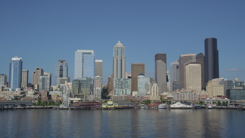 5K stock footage aerial video of low altitude view of the Downtown Seattle skyline and the Central Waterfront, seen from Elliott Bay, Washington Aerial Stock Footage | AX47_098
