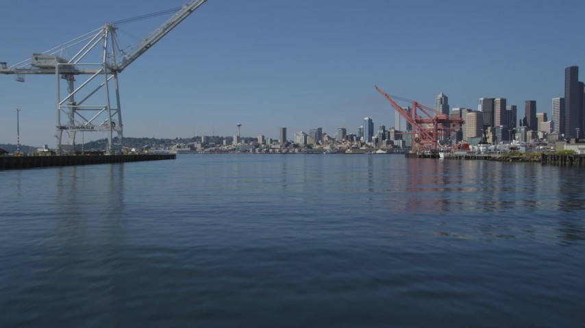 5K stock footage aerial video fly low over between Harbor Island cargo cranes, and approach the Seattle skyline, Washington Aerial Stock Footage | AX47_105