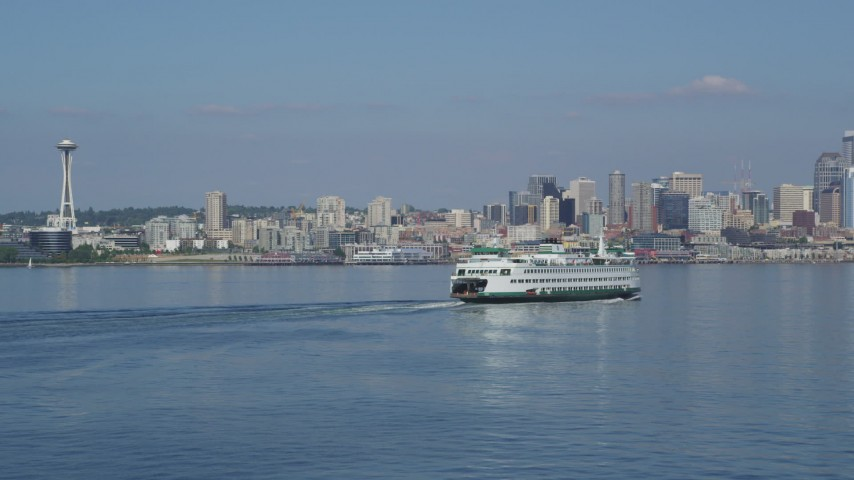 5K stock footage aerial video fly low to approach and pass a ferry sailing toward the Downtown Seattle skyline in Washington Aerial Stock Footage | AX47_117