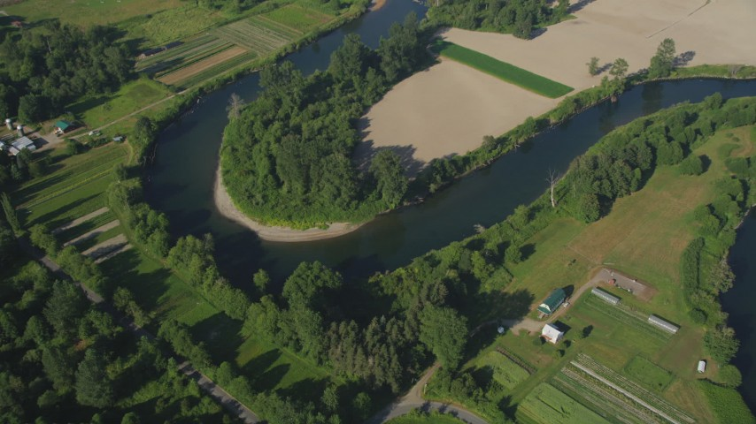 5K stock footage aerial video tilt to a bird's eye view of the Snoqualmie River and farmland in Carnation, Washington Aerial Stock Footage | AX48_028