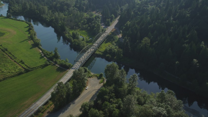 5K stock footage aerial video fly over a green field to approach a small bridge spanning the Snoqualmie River in Carnation, Washington Aerial Stock Footage | AX48_030