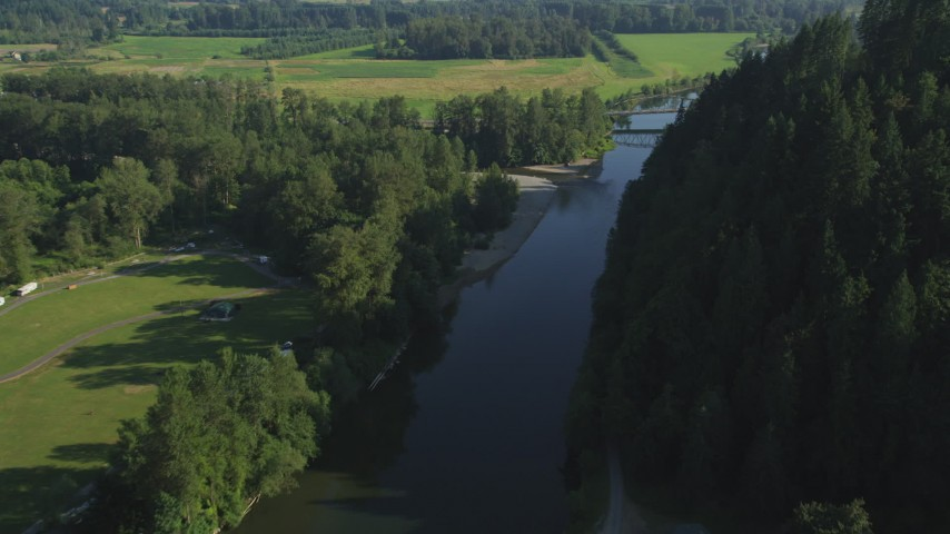 5K stock footage aerial video fly over a bridge on the Snoqualmie River to approach a second bridge in Carnation, Washington Aerial Stock Footage | AX48_032