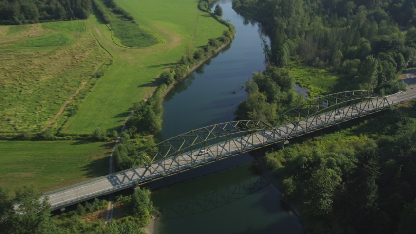 5K stock footage aerial video approach a bridge spanning the Snoqualmie River and tilt to a bird's eye view in Carnation, Washington Aerial Stock Footage | AX48_033
