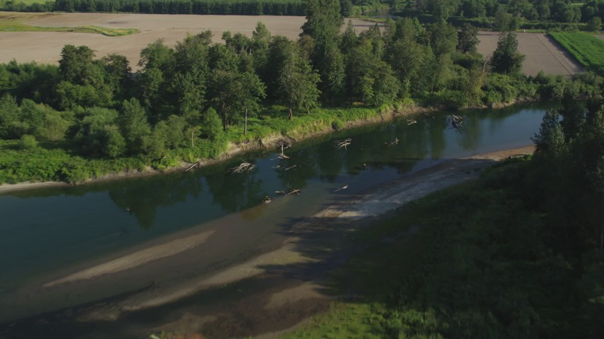 5K stock footage aerial video fly over the Snoqualmie River and a farm field in Carnation, Washington Aerial Stock Footage | AX48_036
