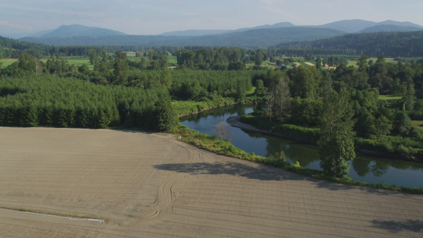 5K stock footage aerial video fly over the Snoqualmie River to approach farm fields in Carnation, Washington Aerial Stock Footage | AX48_037