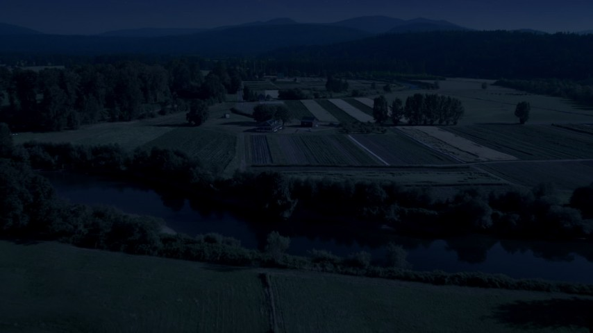 Day for night color corrected aerial footage of the Snoqualmie River and farm fields in Carnation, Washington  Aerial Stock Footage | AX48_037_DFN