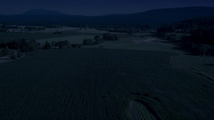 Day for night color corrected aerial footage of crop fields and a country road near a greenhouse in Carnation, Washington Aerial Stock Footage | AX48_040_DFN