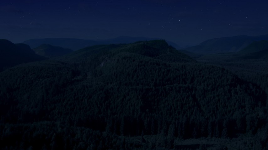Day for night color corrected aerial footage of flying over a wooded mountain in King County, Seattle, Washington Aerial Stock Footage AX48_053_DFN