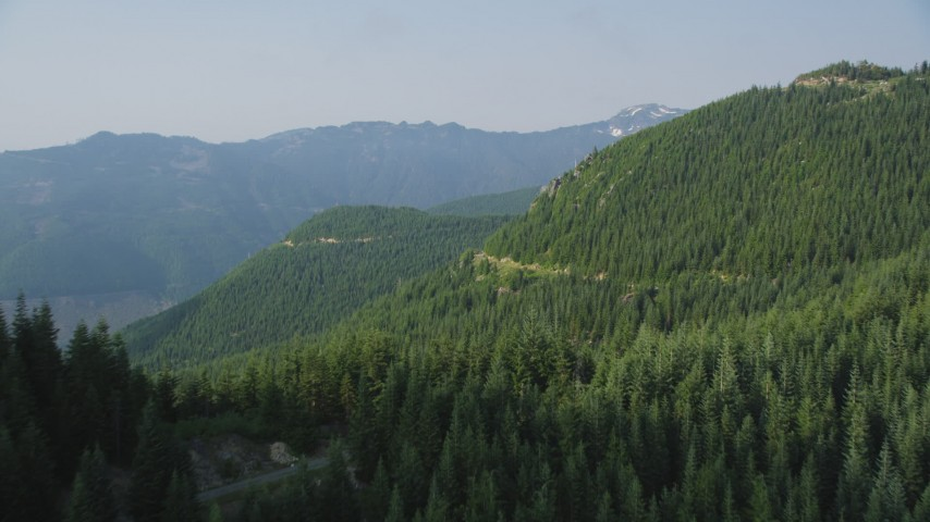 5K stock footage aerial video fly over a mountain ridge and by evergreen trees on mountain slopes, Cascade Range, Washington Aerial Stock Footage | AX48_063