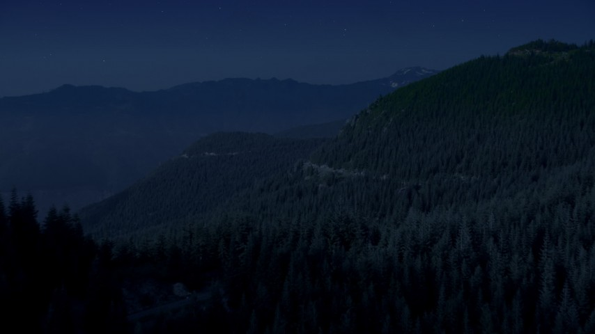 4K day for night color corrected aerial footage of a mountain ridge and evergreen trees on mountain slopes, Cascade Range, Washington Aerial Stock Footage | AX48_063_DFN