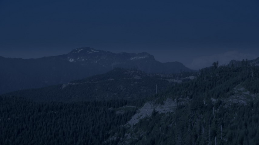 4K day for night color corrected aerial footage of evergreen trees on the slope of a mountain ridge in the Cascade Range, Washington Aerial Stock Footage | AX48_064_DFN