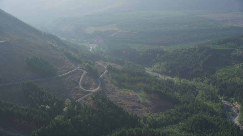 5K aerial video fly over forest and logging area to approach a road at the base of a mountain in King County, Washington Aerial Stock Footage | AX48_066