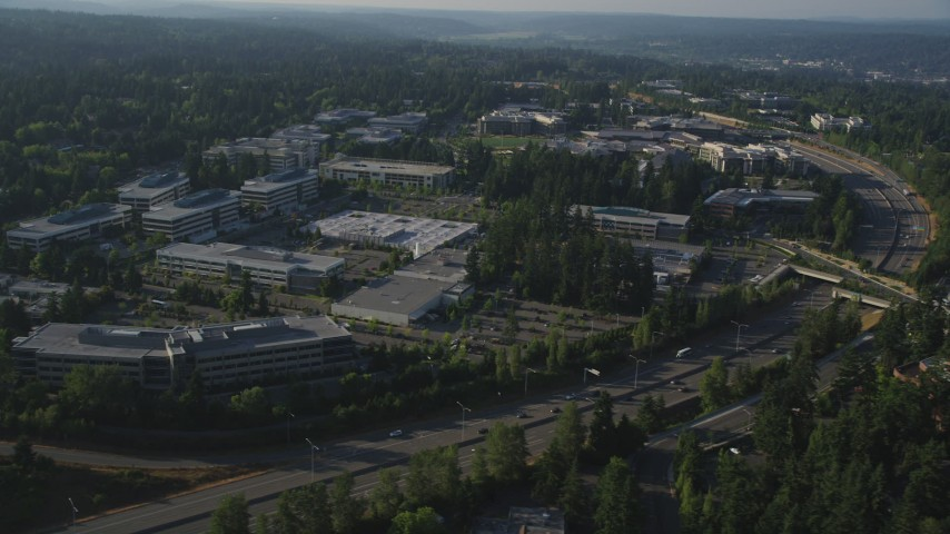 5K stock footage aerial video of passing by Microsoft Headquarters office complex beside freeway with light traffic in Redmond, Washington Aerial Stock Footage | AX49_045