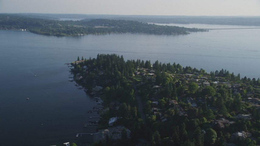5K aerial video of flying by lakeside homes with docks on the shore of Lake Washington, Bellevue, Washington Aerial Stock Footage | AX49_052