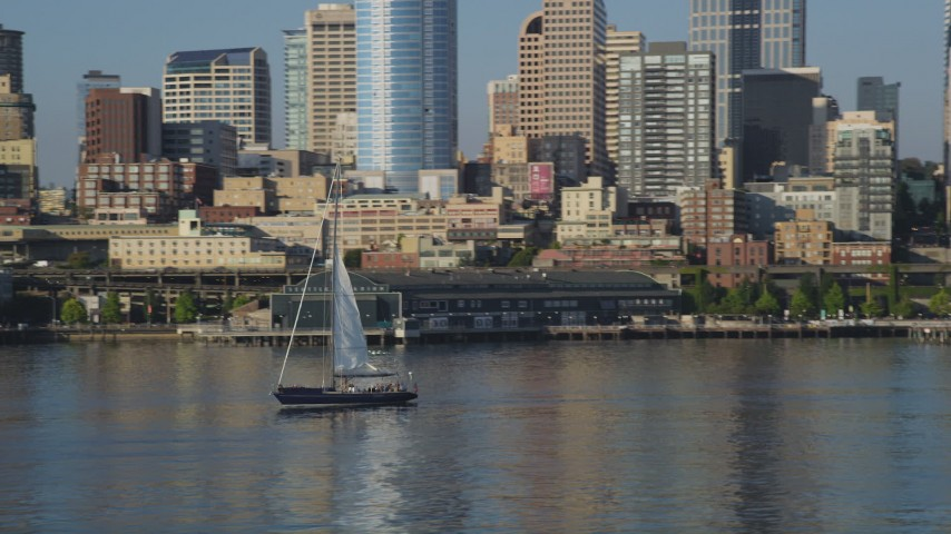 5K stock footage aerial video orbit a sailboat on Elliott Bay, the Central Waterfront, and downtown skyscrapers, Downtown Seattle, Washington Aerial Stock Footage | AX49_068