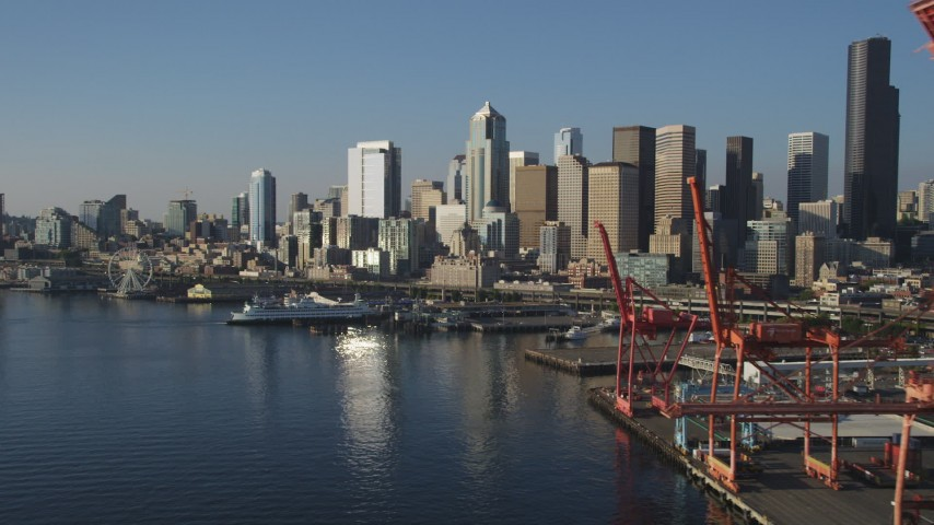 5K stock footage aerial video of the Central Waterfront and Downtown Seattle skyline, reveal cargo cranes, Washington Aerial Stock Footage | AX49_083