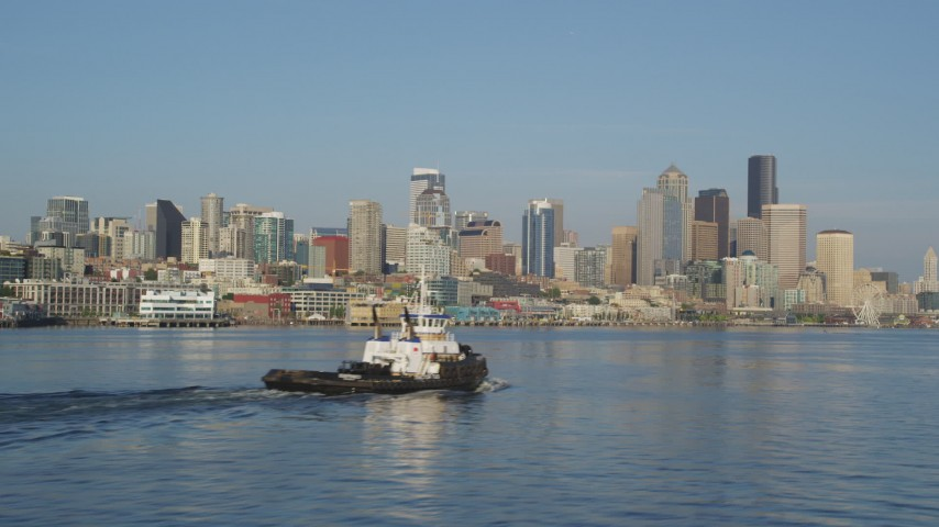 5K stock footage aerial video of Downtown Seattle skyline, seen while passing a tugboat on Elliott Bay, Washington Aerial Stock Footage | AX49_090