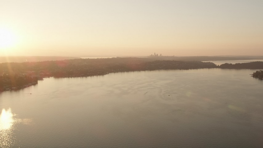 5K stock footage aerial video fly over Lake Washington toward the distant Downtown Seattle skyline in the distance, sunset Aerial Stock Footage | AX50_003