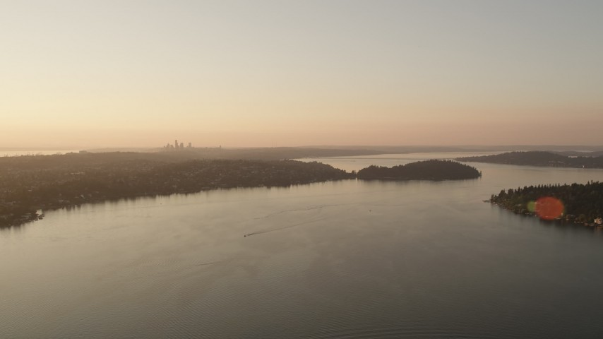 5K aerial video of the distant Downtown Seattle skyline seen while flying over Lake Washington at sunset Aerial Stock Footage | AX50_004