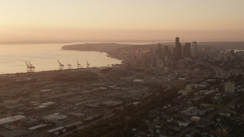 5K stock footage aerial video approach CenturyLink, Safeco Field, port cargo cranes, and skyscrapers, Downtown Seattle, Washington, sunset Aerial Stock Footage | AX50_006