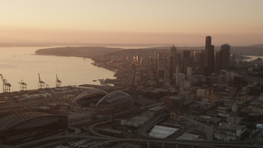 5K stock footage aerial video flyby CenturyLink and Safeco Fields toward skyscrapers in Downtown Seattle, Washington, sunset Aerial Stock Footage | AX50_007