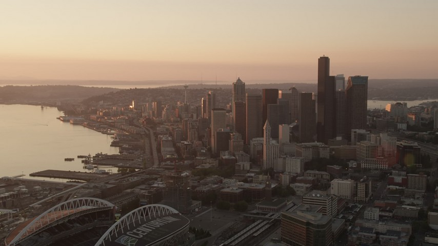 5K stock footage aerial video fly over CenturyLink Field to approach Downtown Seattle skyscrapers, Washington, sunset Aerial Stock Footage | AX50_008