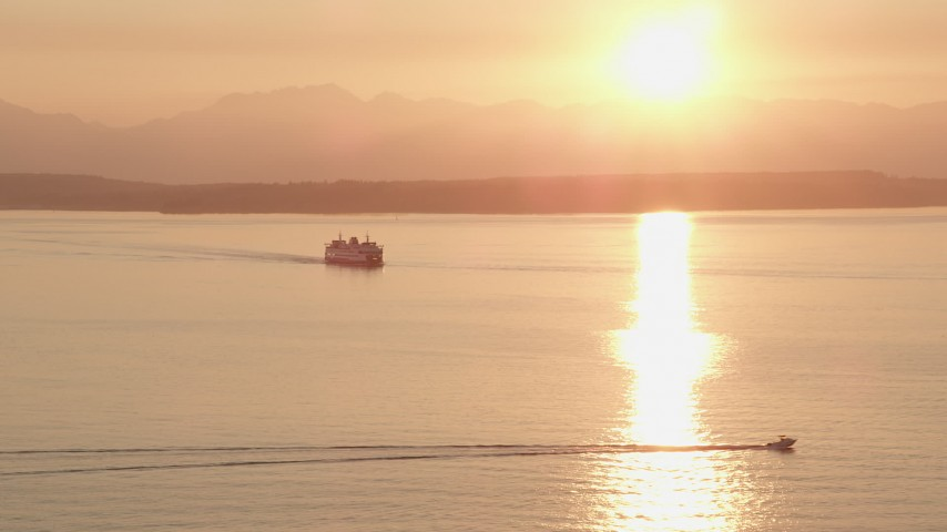 5K stock footage aerial video of setting sun over a ferry sailing Elliott Bay, Washington, sunset Aerial Stock Footage | AX50_013