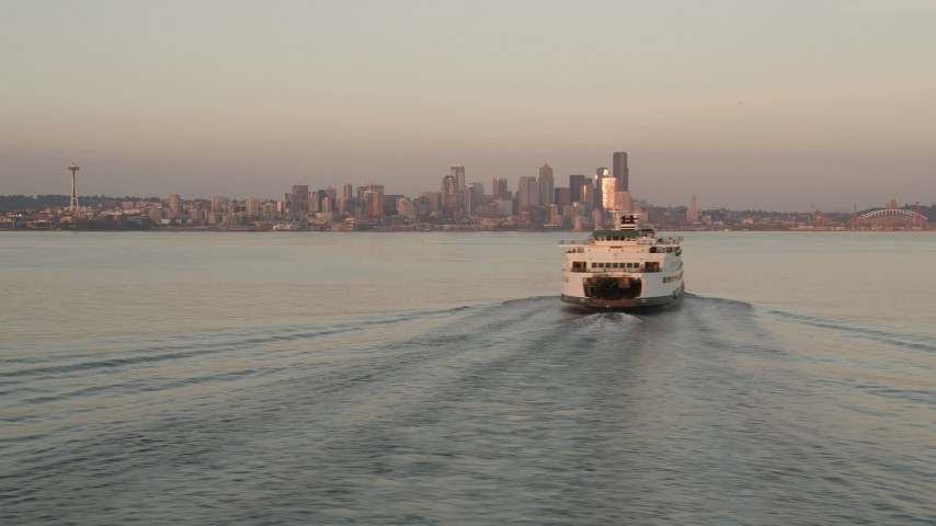 5K stock footage aerial video fly low by a ferry sailing Elliott Bay to reveal Downtown Seattle skyline, Washington, sunset Aerial Stock Footage | AX50_016