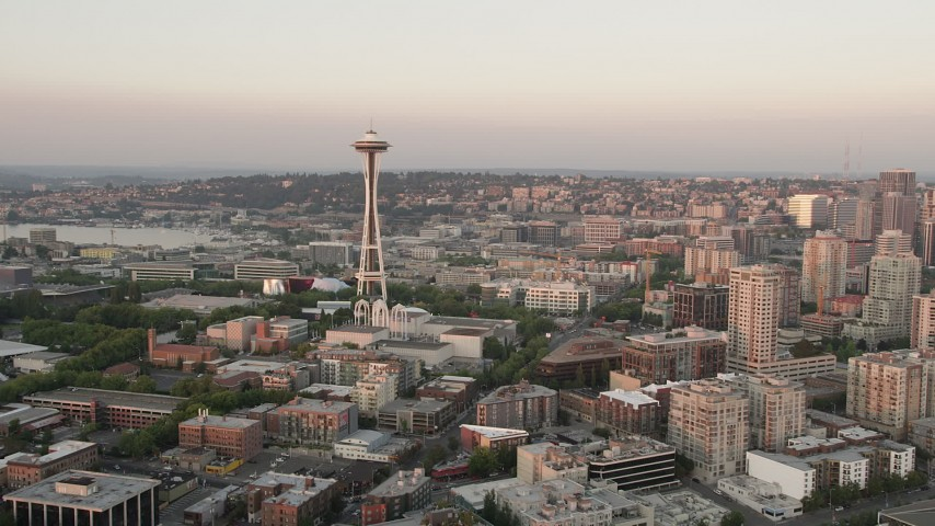 5K stock footage aerial video fly over the shore of Elliott Bay to approach the Space Needle in Downtown Seattle, Washington, sunset Aerial Stock Footage | AX50_020